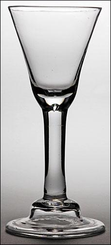 An Irish plain stem goblet (c. 1740). trumpet bowl with small tear at the base